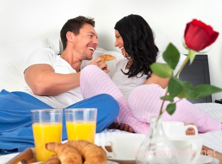 Happy romantic couple eating breakfast in bed laughing