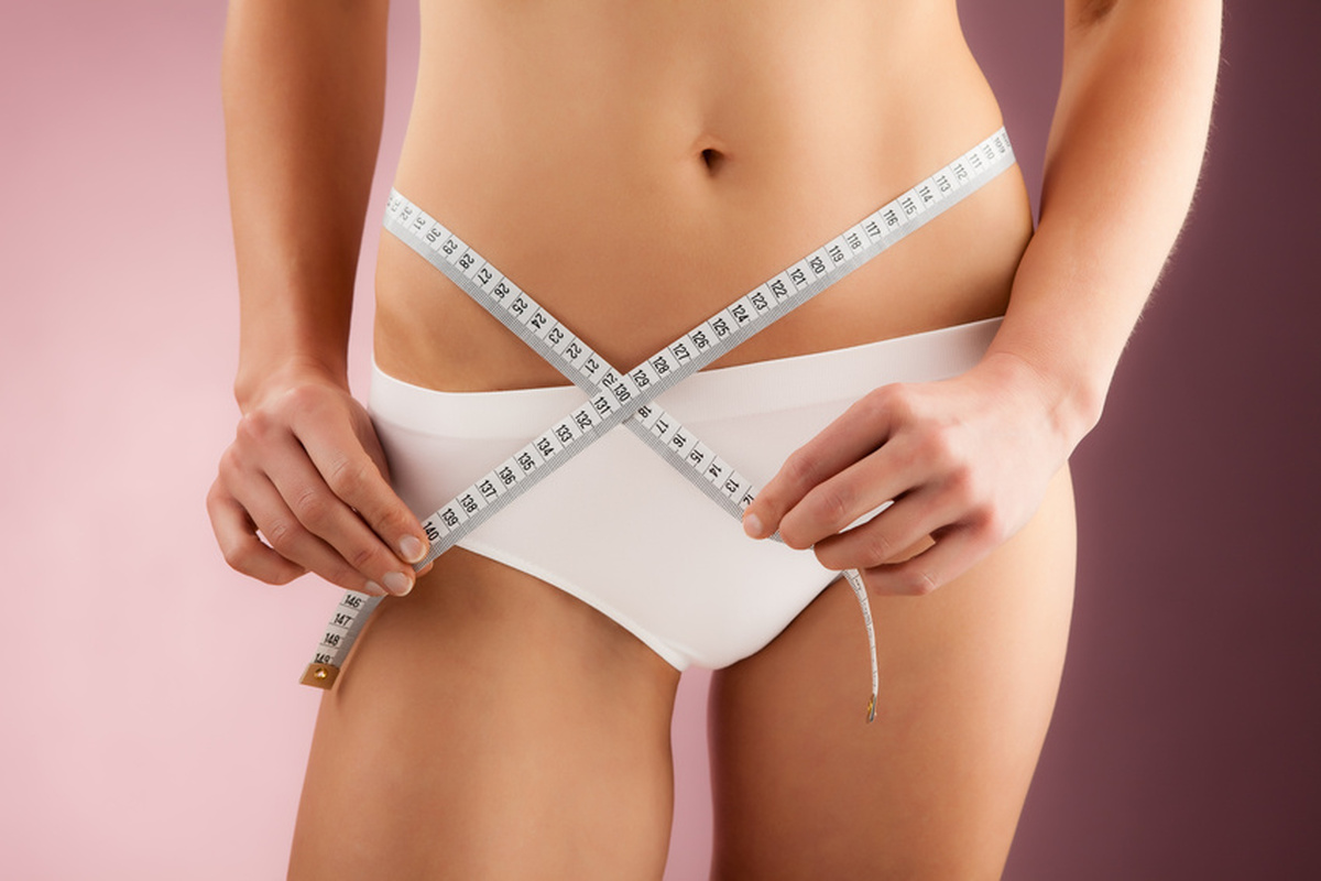 Woman measuring her slim body