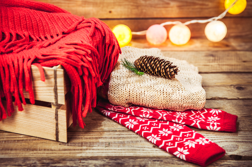 Christmas set. Warm blanket, sweater, socks, garland and a bump on the wooden background