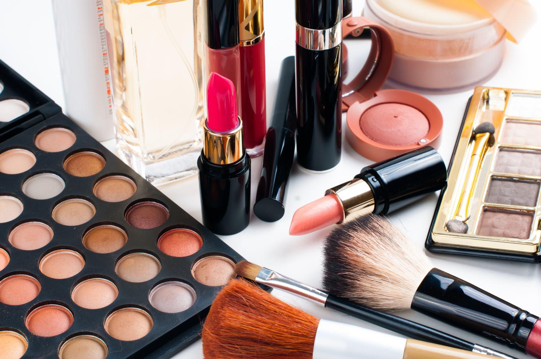 Professional makeup set: eyeshadow palette, lipstick, mascara, blush, powder, make-up brushes and perfume, many cosmetics closeup.