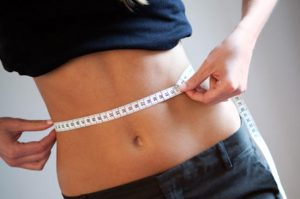 Women measuring waist. Available light shot