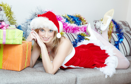 Lady in the red Santa Claus costume laying indoors near the Christmas gifts