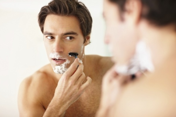 Portrait of a handsome young man looking at self in the mirror and shaving