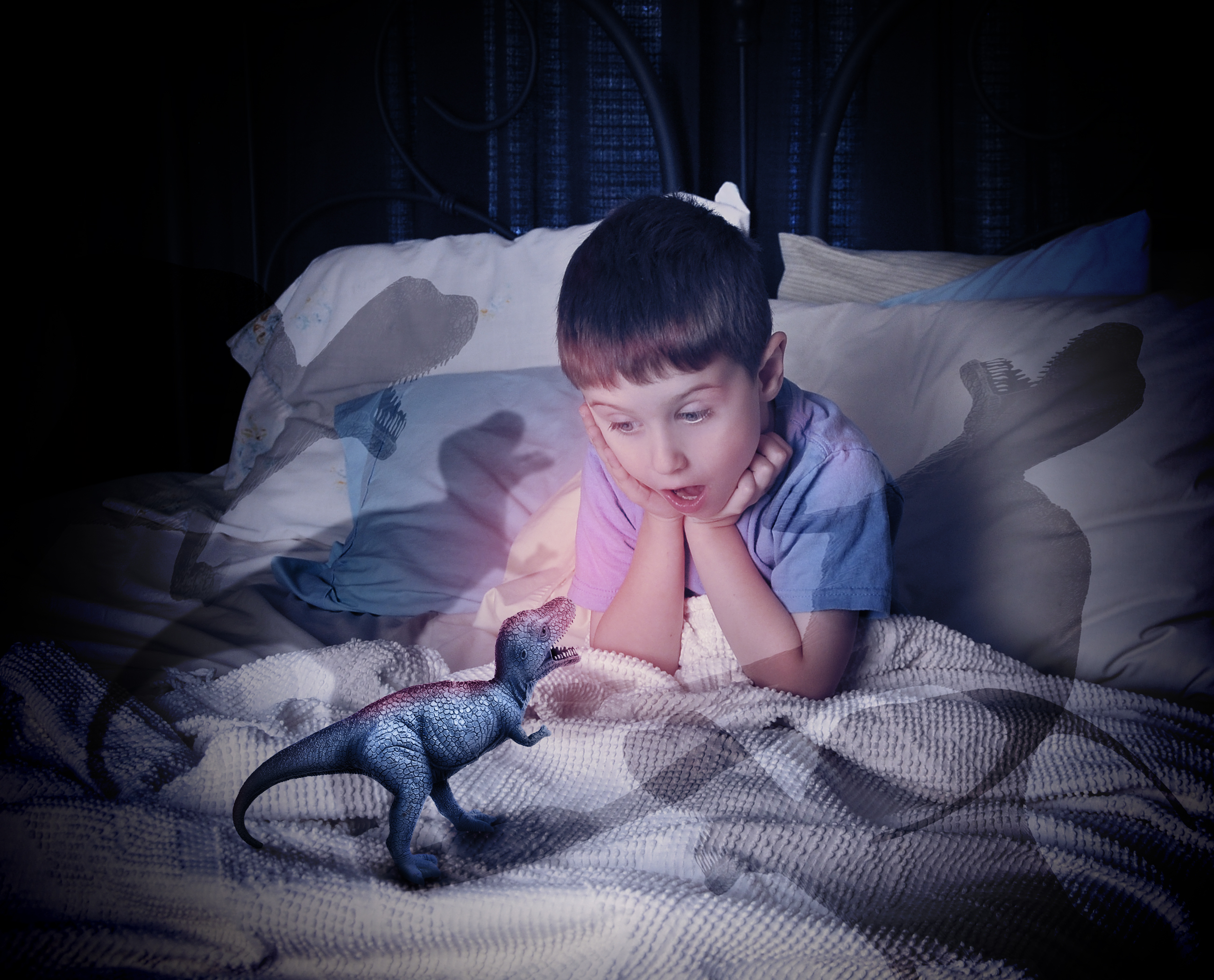 A little boy is looking at a t-red dinosaur toy on his bed that is scary with shadows for a bedtime fear concept.