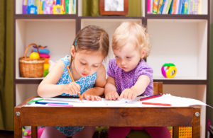 two beautiful little girl drawing near the table