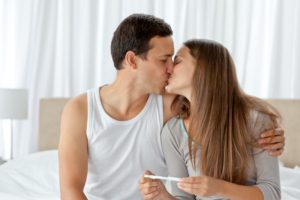Couple kissing after looking at the result of a pregnancy test in the bedroom
