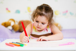 child writing with felt-tip pen