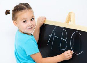 Cute little girl is showing letter E on the alphabet in preschool