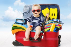 39545903 - baby in travel suitcase. kid inside luggage packed for vacation full of clothes, child and family trip