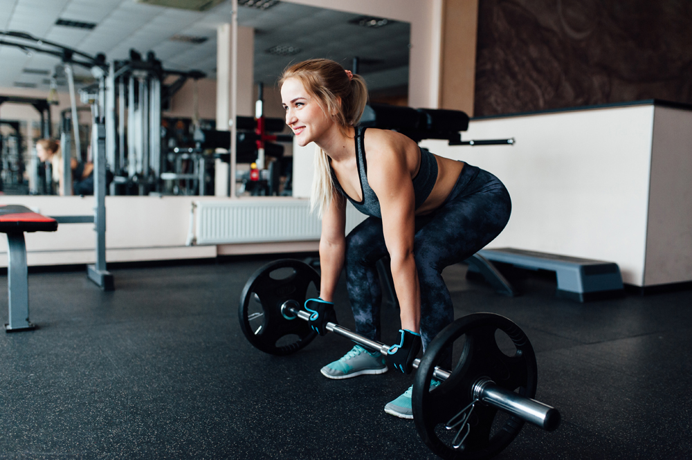 Beautiful fitness woman lifting barbell. Sporty woman lifting weights. Fit girl exercising building muscles. Fitness and bodybuilding. side view