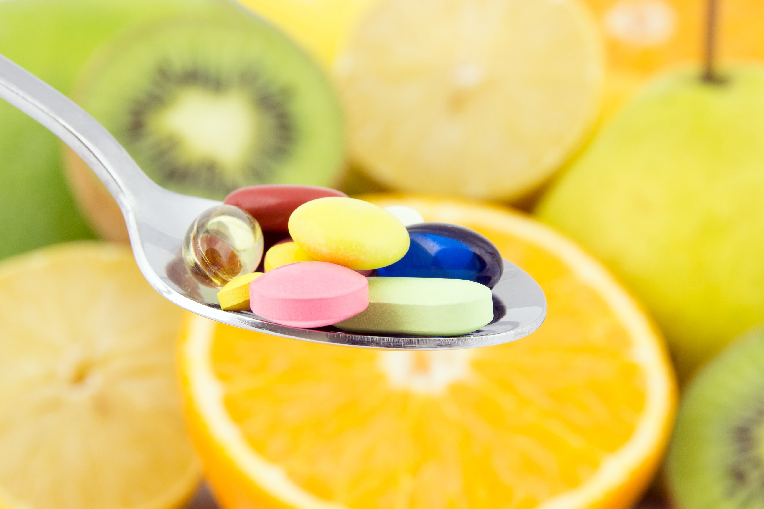 Spoon full of colorful pills against the background of fresh fruits