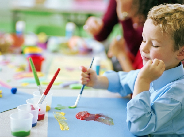 Schoolboy (4-6) painting at table, smiling